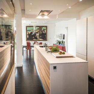 Exemple d'une cuisine américaine linéaire tendance de taille moyenne avec un îlot central, un évier intégré, des portes de placard blanches, un plan de travail en stratifié, un plan de travail blanc, un électroménager encastrable et un sol noir.