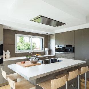 Immagine di una cucina minimal con lavello integrato, ante marroni, top in laminato, paraspruzzi marrone, elettrodomestici in acciaio inossidabile, pavimento in legno massello medio, isola, pavimento marrone e top bianco