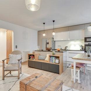 Inspiration pour une cuisine ouverte parallèle design avec un placard à porte plane, des portes de placard blanches, un électroménager en acier inoxydable, un sol en bois clair, un îlot central, un sol beige et un plan de travail gris.
