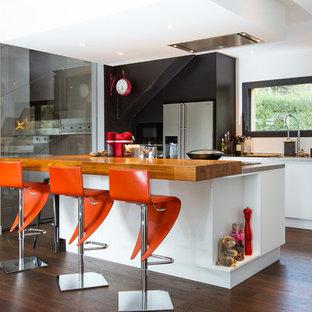 Idées déco pour une cuisine parallèle contemporaine avec un évier encastré, un placard à porte plane, des portes de placard blanches, un électroménager en acier inoxydable, un sol en bois foncé, un îlot central et un sol marron.