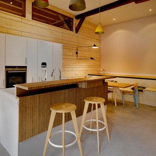 Cette image montre une cuisine design avec un placard à porte plane, des portes de placard blanches, béton au sol, un îlot central et un sol gris.