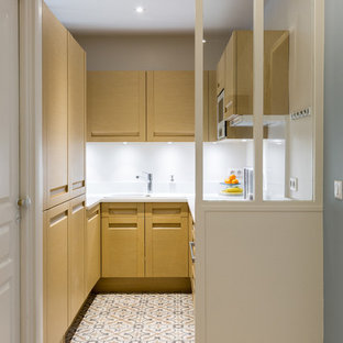 Design ideas for a small scandinavian u-shaped enclosed kitchen in Paris with a built-in sink, light wood cabinets, white splashback, integrated appliances and no island.