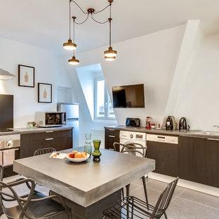 Cette photo montre une grande cuisine américaine tendance en L avec un évier 1 bac, des portes de placard noires, une crédence noire, un électroménager encastrable, un sol en carrelage de céramique et un îlot central.