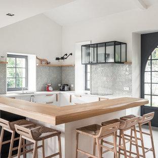 Idées déco pour une cuisine scandinave en L avec un placard à porte plane, des portes de placard blanches, un plan de travail en bois, une crédence multicolore, béton au sol, une péninsule et un sol gris.