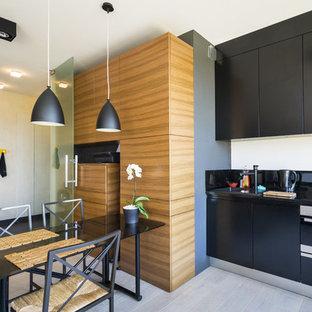 Inspiration pour une cuisine américaine linéaire design de taille moyenne avec des portes de placard noires et aucun îlot.