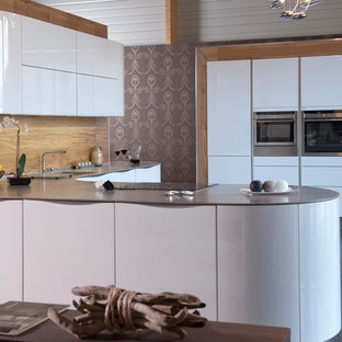 Photo of a large transitional l-shaped open plan kitchen in Angers with an integrated sink, white cabinets, panelled appliances and a peninsula.