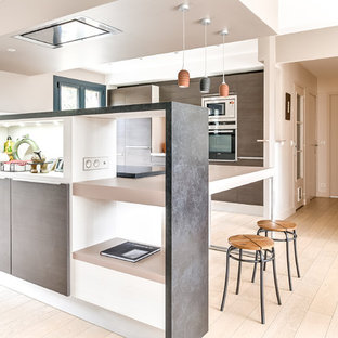 Photo of a large modern l-shaped kitchen/diner in Lyon with a submerged sink, flat-panel cabinets, medium wood cabinets, granite worktops, orange splashback, stainless steel appliances, light hardwood flooring and a breakfast bar.