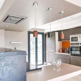 リヨンの広いモダンスタイルのおしゃれなキッチン (フラットパネル扉のキャビネット、中間色木目調キャビネット、御影石カウンター、アンダーカウンターシンク、オレンジのキッチンパネル、木材のキッチンパネル、シルバーの調理設備、淡色無垢フローリング、ベージュの床、グレーのキッチンカウンター) の写真