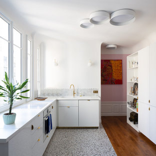 Bild på ett mellanstort funkis vit vitt l-kök, med vita skåp, laminatbänkskiva, grått stänkskydd, stänkskydd i marmor, terrazzogolv, en nedsänkt diskho, släta luckor och flerfärgat golv