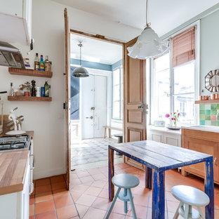 Idée de décoration pour une grande cuisine parallèle bohème fermée avec un évier 2 bacs, un placard à porte shaker, des portes de placard en bois clair, une crédence multicolore, une crédence en mosaïque, un sol en carreau de terre cuite et un îlot central.