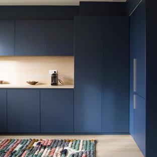 パリのコンテンポラリースタイルのおしゃれなL型キッチン (フラットパネル扉のキャビネット、青いキャビネット、木材カウンター、ベージュキッチンパネル、木材のキッチンパネル、淡色無垢フローリング、ベージュの床、ベージュのキッチンカウンター) の写真