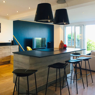 Large contemporary l-shaped eat-in kitchen in Rennes with an integrated sink, beaded inset cabinets, light wood cabinets, granite benchtops, black splashback, limestone splashback, black appliances, light hardwood floors, with island, brown floor and black benchtop.