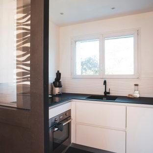 Foto di una cucina costiera con lavello sottopiano, ante lisce, ante bianche, top in superficie solida, paraspruzzi bianco, paraspruzzi con piastrelle in ceramica, elettrodomestici in acciaio inossidabile, pavimento in terracotta, pavimento nero e top nero