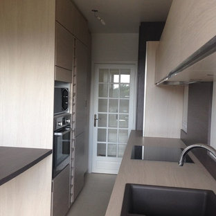 This is an example of a mid-sized traditional single-wall separate kitchen in Paris with a double-bowl sink, flat-panel cabinets, light wood cabinets, laminate benchtops, brown splashback, panelled appliances, ceramic floors, no island, beige floor and beige benchtop.