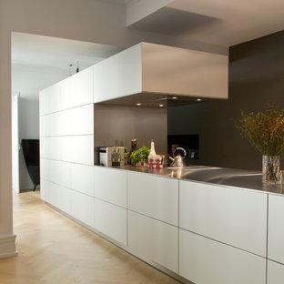 Idée de décoration pour une grand cuisine ouverte linéaire design avec des portes de placard blanches et aucun îlot.