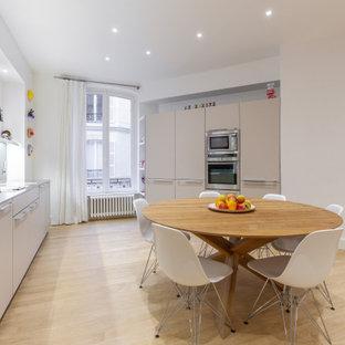 Aménagement d'une grand cuisine ouverte linéaire contemporaine avec un évier encastré, un placard à porte affleurante, des portes de placard beiges, un plan de travail en inox, une crédence grise, un sol en bois clair, aucun îlot et un plan de travail gris.