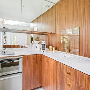 Inspiration pour une cuisine design en L avec un évier 1 bac, un placard à porte plane, des portes de placard en bois brun, une crédence en carreau de miroir, un électroménager en acier inoxydable, aucun îlot et un plan de travail blanc.