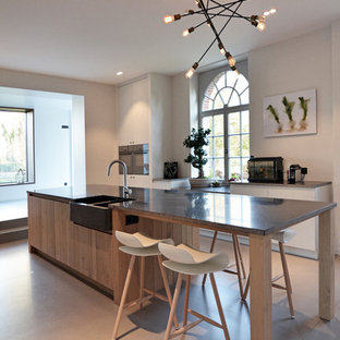 Inspiration for a large contemporary galley eat-in kitchen in Paris with a farmhouse sink, with island, panelled appliances, beaded inset cabinets, light wood cabinets, granite benchtops, black splashback, terra-cotta splashback and concrete floors.