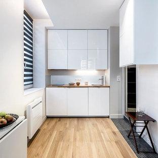 Inspiration för små moderna linjära kök med öppen planlösning, med en nedsänkt diskho, vita skåp, träbänkskiva, stänkskydd med metallisk yta, stänkskydd i metallkakel och ljust trägolv