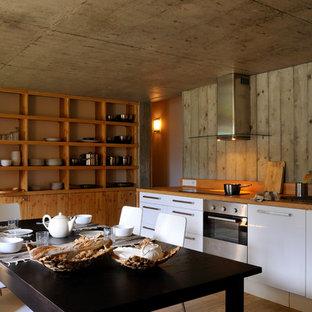 Aménagement d'une grande cuisine américaine éclectique en L avec un placard à porte plane, des portes de placard blanches, un plan de travail en bois, un sol en bois brun et aucun îlot.