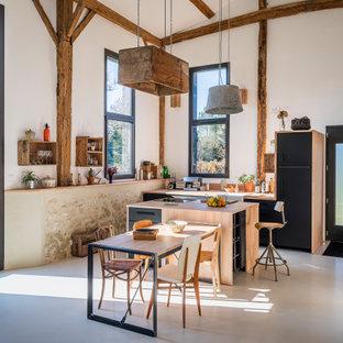 ボルドーのカントリー風おしゃれなキッチン (エプロンフロントシンク、フラットパネル扉のキャビネット、黒いキャビネット、木材カウンター、パネルと同色の調理設備、コンクリートの床、グレーの床、ベージュのキッチンカウンター) の写真