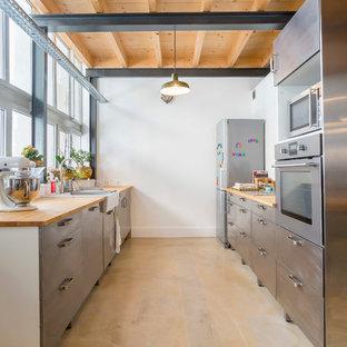Cette image montre une grande cuisine parallèle urbaine fermée avec un évier de ferme, un placard à porte plane, une façade en inox, un électroménager en acier inoxydable, aucun îlot et un plan de travail en bois.