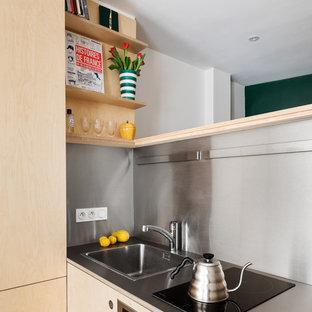 Modelo de cocina lineal, contemporánea, pequeña, abierta, con fregadero bajoencimera, puertas de armario de madera clara, encimera de acero inoxidable, electrodomésticos de acero inoxidable, suelo de linóleo, dos o más islas y suelo azul