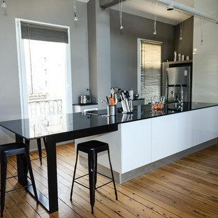 Cette photo montre une cuisine américaine parallèle tendance de taille moyenne avec un sol en bois brun et un îlot central.