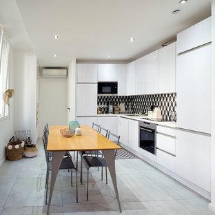 Idée de décoration pour une cuisine américaine design en L avec un évier encastré, un placard à porte plane, des portes de placard blanches, une crédence multicolore, un électroménager en acier inoxydable, aucun îlot et un sol gris.