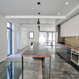 This is an example of a large contemporary galley open plan kitchen in Paris with an undermount sink, flat-panel cabinets, black cabinets, wood benchtops, beige splashback, mosaic tile splashback, ceramic floors, with island, grey floor, stainless steel appliances and red benchtop.