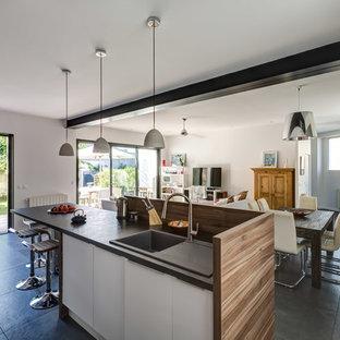 Aménagement d'une cuisine ouverte parallèle contemporaine de taille moyenne avec des portes de placard blanches, un sol en carrelage de céramique et un îlot central.