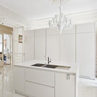 Cette photo montre une cuisine tendance fermée et de taille moyenne avec un évier 2 bacs, un placard à porte plane, des portes de placard blanches, un sol en marbre et un îlot central.