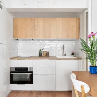 Cette image montre une cuisine ouverte design en L avec un évier posé, un placard à porte plane, des portes de placard blanches, un plan de travail en bois, une crédence blanche, une crédence en carrelage métro, un électroménager encastrable, un sol en bois clair et une péninsule.