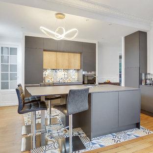 Cette photo montre une cuisine tendance avec un évier encastré, un placard à porte plane, des portes de placard grises, une crédence multicolore, un sol en bois clair, un îlot central et un plan de travail gris.
