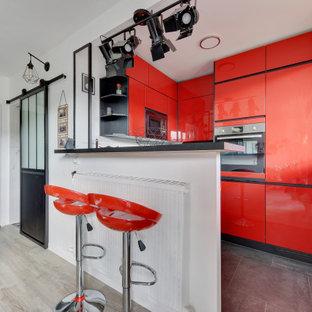 Cette photo montre une cuisine tendance en U avec un placard à porte plane, des portes de placard rouges, un électroménager en acier inoxydable, une péninsule et un sol gris.