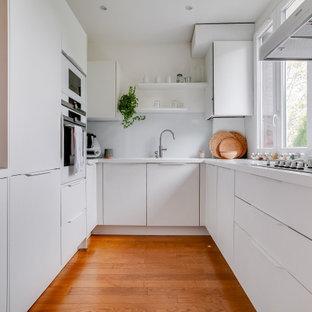 Idées déco pour une petite cuisine ouverte contemporaine en U avec des portes de placard blanches, un plan de travail en quartz, une crédence blanche, une crédence en carreau de verre, un électroménager blanc, un sol en bambou, un sol marron, un plan de travail blanc, un évier posé, un placard à porte plane et aucun îlot.