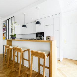 Inspiration pour une petit cuisine ouverte design en U avec un placard à porte plane, des portes de placard blanches, un plan de travail en bois, une crédence blanche, un électroménager en acier inoxydable, un sol en bois clair, une péninsule, un sol marron, un plan de travail marron et un évier encastré.