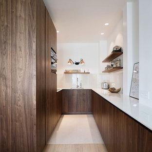 Cette photo montre une cuisine moderne en U avec un évier encastré, un placard à porte plane, des portes de placard en bois sombre, aucun îlot, un sol beige et un plan de travail blanc.