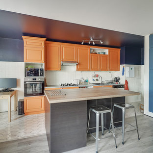 Idée de décoration pour une cuisine linéaire bohème avec un évier 2 bacs, un placard avec porte à panneau surélevé, des portes de placard oranges, une crédence blanche, un îlot central et un plan de travail gris.