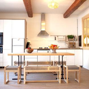 Idées déco pour une cuisine américaine linéaire scandinave de taille moyenne avec un évier posé, un placard à porte plane, des portes de placard blanches, un plan de travail en bois, une crédence blanche, un sol en bois brun, aucun îlot, un sol marron et un plan de travail marron.