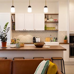 This is an example of a mid-sized midcentury single-wall open plan kitchen in Paris with a single-bowl sink, raised-panel cabinets, white cabinets, wood benchtops, white splashback, subway tile splashback, stainless steel appliances, ceramic floors, with island, brown benchtop and beige floor.