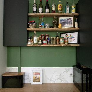 Industriell inredning av ett litet beige beige kök, med vitt stänkskydd, stänkskydd i marmor, grått golv, en undermonterad diskho, släta luckor, svarta skåp, träbänkskiva, svarta vitvaror, klinkergolv i keramik och flera köksöar