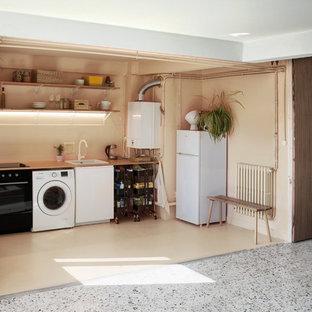 Cette photo montre une cuisine industrielle avec un évier encastré, un plan de travail en bois et un sol en terrazzo.
