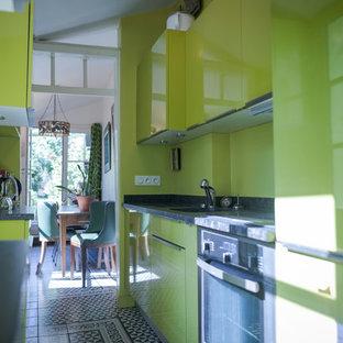 Foto di una cucina design di medie dimensioni con lavello integrato, ante a filo, ante verdi, top in quarzite, paraspruzzi verde, elettrodomestici da incasso, pavimento in cementine, nessuna isola, pavimento nero e top nero