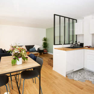 Design ideas for a mid-sized scandinavian l-shaped eat-in kitchen in Bordeaux with a drop-in sink, flat-panel cabinets, white cabinets, wood benchtops, white splashback, subway tile splashback, black appliances, light hardwood floors, no island, beige floor and beige benchtop.