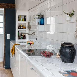 パリの中サイズのコンテンポラリースタイルのおしゃれなキッチン (フラットパネル扉のキャビネット、白いキャビネット、タイルカウンター、白いキッチンパネル、磁器タイルのキッチンパネル、パネルと同色の調理設備、淡色無垢フローリング、ベージュの床、白いキッチンカウンター、アンダーカウンターシンク、アイランドなし) の写真