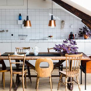 パリの中くらいのコンテンポラリースタイルのおしゃれなキッチン (フラットパネル扉のキャビネット、白いキャビネット、タイルカウンター、白いキッチンパネル、磁器タイルのキッチンパネル、パネルと同色の調理設備、淡色無垢フローリング、ベージュの床、白いキッチンカウンター、アンダーカウンターシンク、アイランドなし) の写真