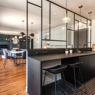 Foto di una cucina contemporanea di medie dimensioni con lavello sottopiano, ante nere, pavimento in gres porcellanato, isola, pavimento nero, top nero e paraspruzzi nero
