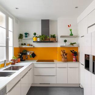 Bild på ett mellanstort funkis vit vitt l-kök, med en dubbel diskho, släta luckor, vita skåp, bänkskiva i glas, integrerade vitvaror, klinkergolv i keramik, grått golv, orange stänkskydd och glaspanel som stänkskydd