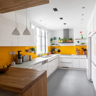Inspiration for a mid-sized contemporary l-shaped separate kitchen in Paris with a double-bowl sink, flat-panel cabinets, white cabinets, glass benchtops, yellow splashback, glass tile splashback, panelled appliances, ceramic floors, no island, grey floor and white benchtop.